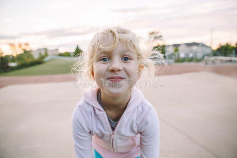 Aanbiddelijk weinig kind die van het blonde Kaukasisch meisje grappig dwaas gezicht maken royalty-vrije stock fotografie