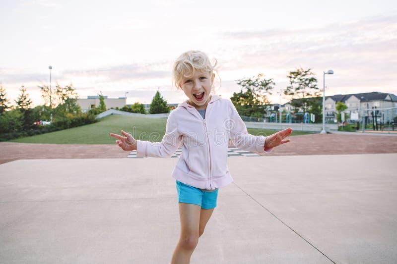 Aanbiddelijk weinig kind die van het blonde Kaukasisch meisje grappig dwaas gezicht maken royalty-vrije stock foto's