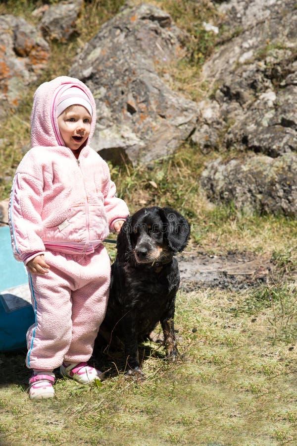 Aanbiddelijk weinig kindmeisje die met huisdierenhond openlucht spelen in park Achtergrond van de de zomer de groene aard stock foto