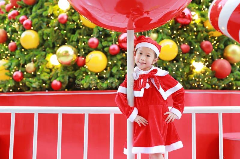 Aanbiddelijk weinig kindmeisje in Kerstmankostuum met heden een Kerstmisachtergrond Vrolijk de vakantieconcept van de Kerstmiswin royalty-vrije stock foto