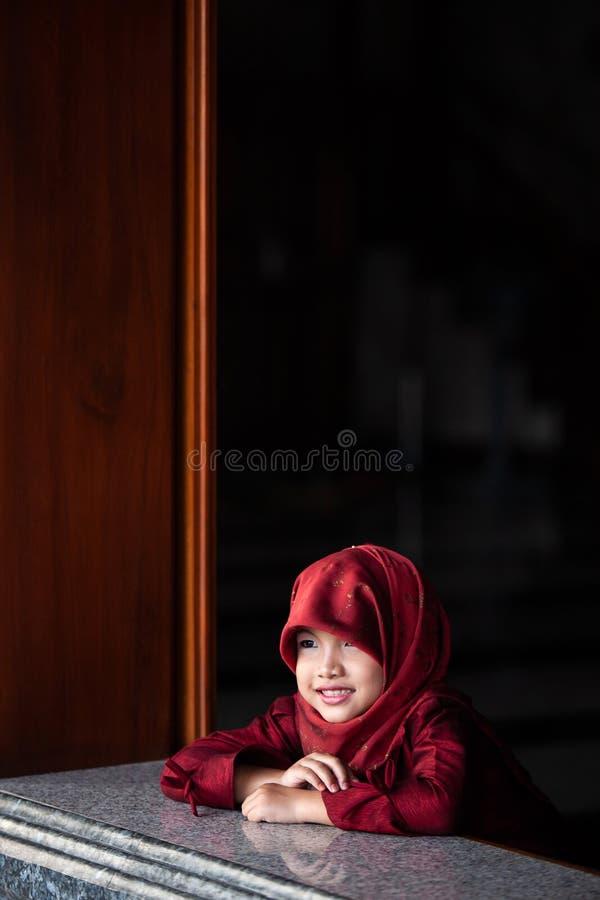 Aanbiddelijk weinig moslimmeisje in traditionele kleding, rode hijab of niqab en rode abaya die en het venster glimlachen oplette stock afbeeldingen