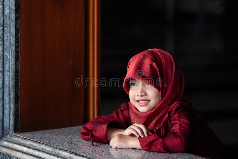 Aanbiddelijk weinig moslimmeisje in traditionele kleding, rode hijab of niqab en rode abaya die en het venster glimlachen oplette royalty-vrije stock foto's