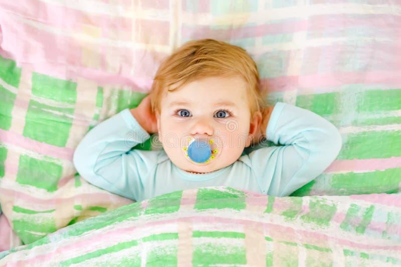 Aanbiddelijk weinig slaap van het babymeisje in bed Kalm vreedzaam kind die tijdens dagslaap dromen Mooie baby in oudersbed stock afbeelding