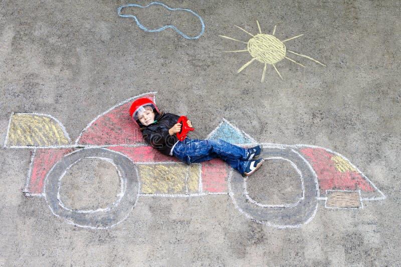 Aanbiddelijk weinig tekening van de jong geitjejongen met het kleurrijke beeld van de krijtraceauto op asfalt royalty-vrije stock foto