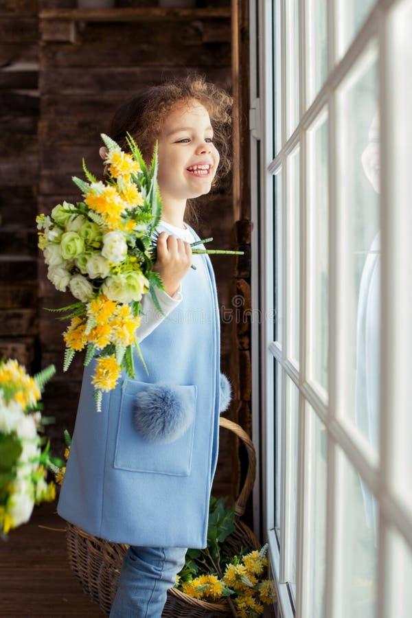 Aanbiddelijk weinig zitting van het kindmeisje op de venster en holdingsbloemen Het meisje bekijkt de blauwe, zuivere hemel en ve royalty-vrije stock foto