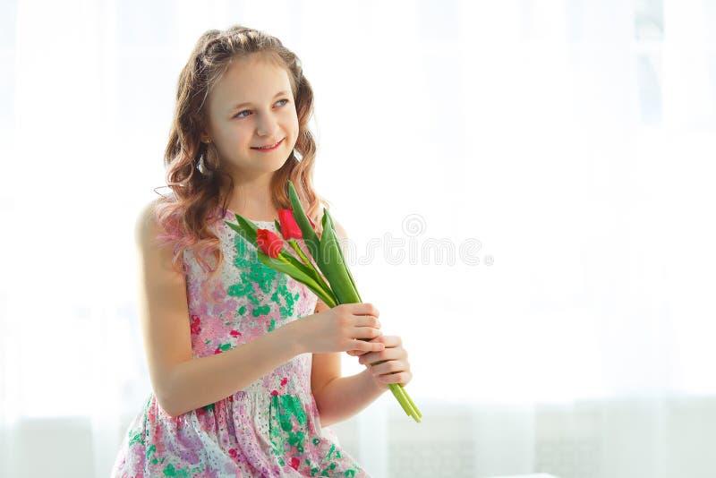 Aanbiddelijk weinig zitting van het tienermeisje op de venster en holdingstulpen stock afbeelding