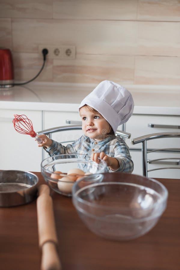 aanbiddelijk zwaait weinig jong geitje in de holding van de chef-kokhoed in hand klaar stock fotografie