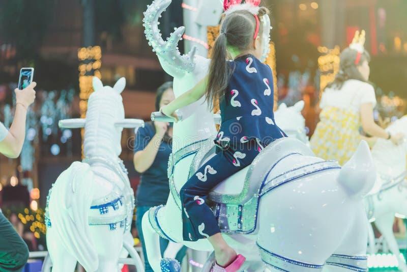 Aanbiddelijke Aziaat weinig jong geitjejongen die op vrolijk berijden gaat om zuipt royalty-vrije stock fotografie