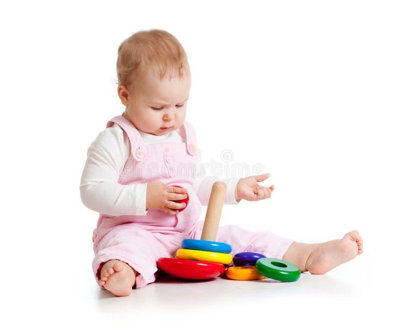 Aanbiddelijke baby die enthousiast woth onderwijsstuk speelgoed spelen Het kleine jonge geitje zit op vloer, op wit stock foto's