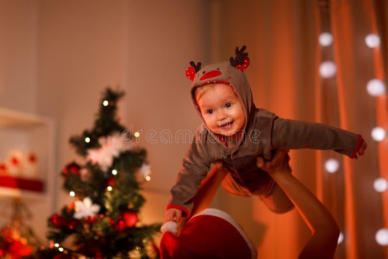 Aanbiddelijke baby die pret heeft dichtbij Kerstboom stock fotografie