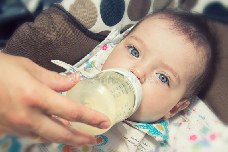 Aanbiddelijke Baby die Van zeven maanden van fles eet stock foto's