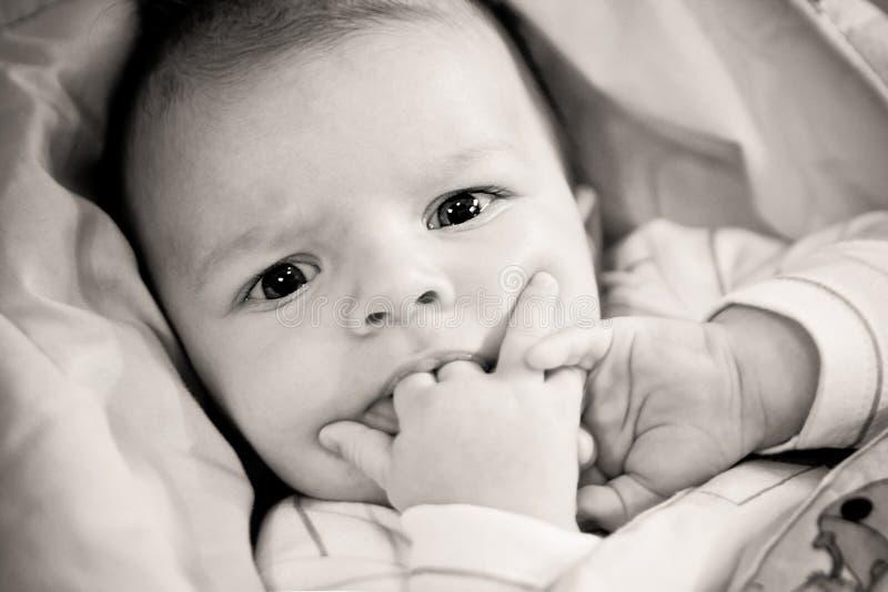 Aanbiddelijke baby met vingers in zijn mond royalty-vrije stock afbeeldingen