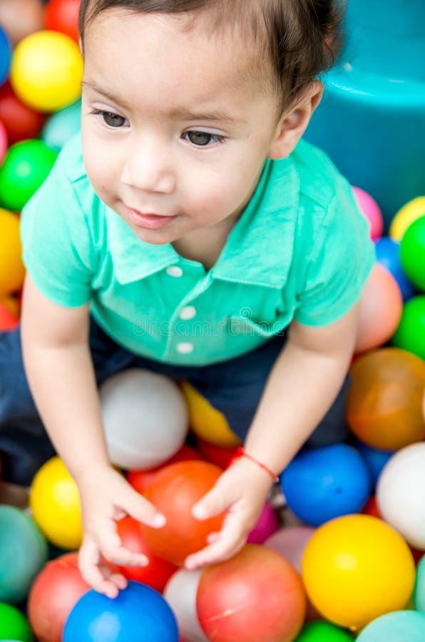 Aanbiddelijke babyjongen die het turkooise t-shirt spelen met gekleurde plastic ballen dragen die vanuit bovengenoemde invalshoek royalty-vrije stock fotografie