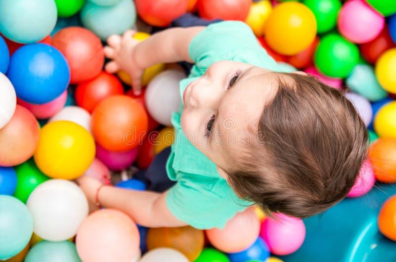Aanbiddelijke babyjongen die het turkooise t-shirt spelen met gekleurde plastic ballen dragen die vanuit bovengenoemde invalshoek royalty-vrije stock afbeeldingen
