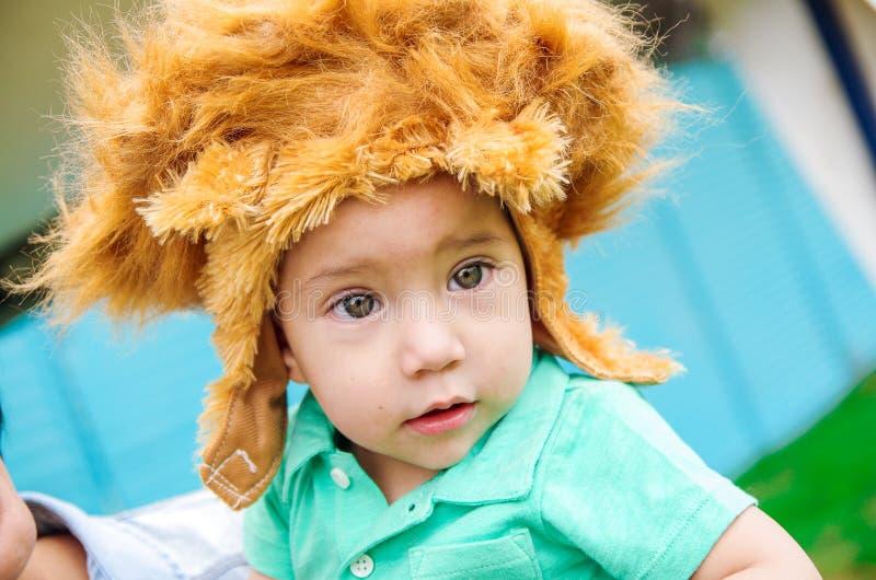 Aanbiddelijke babyjongen die turkooise t-shirt en grote bont bruine hoed dragen royalty-vrije stock foto