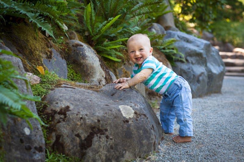 Aanbiddelijke babyjongen die zich op zijn voeten proberen te bevinden royalty-vrije stock afbeeldingen