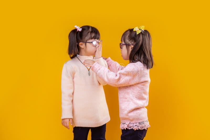 Aanbiddelijke buitengewone kinderen die met benedensyndroom aan elkaar spreken royalty-vrije stock afbeelding