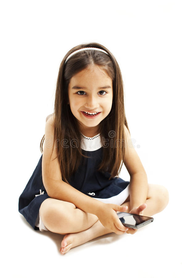 Aanbiddelijke de cel van de meisjeholding telefoon en het glimlachen stock afbeelding