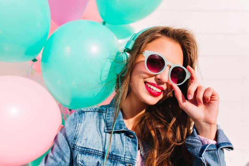 Aanbiddelijke donkerbruine jonge vrouw die door modieuze zonnebril kijken en met glimlach naast kleurrijke ballons stellen sluit stock fotografie