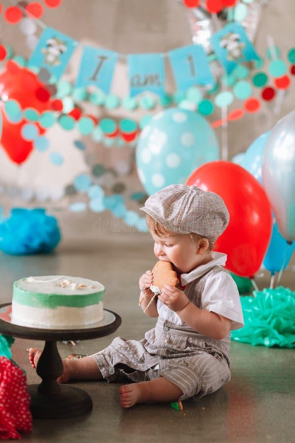 Aanbiddelijke gelukkige babyjongen die cake eten bij zijn eerste verjaardags cakesmash partij royalty-vrije stock foto's