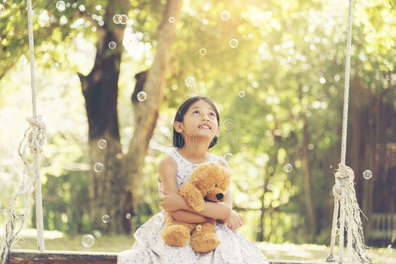 Aanbiddelijke gelukkige leuke meisjeszitting met teddybeer in het park stock foto's