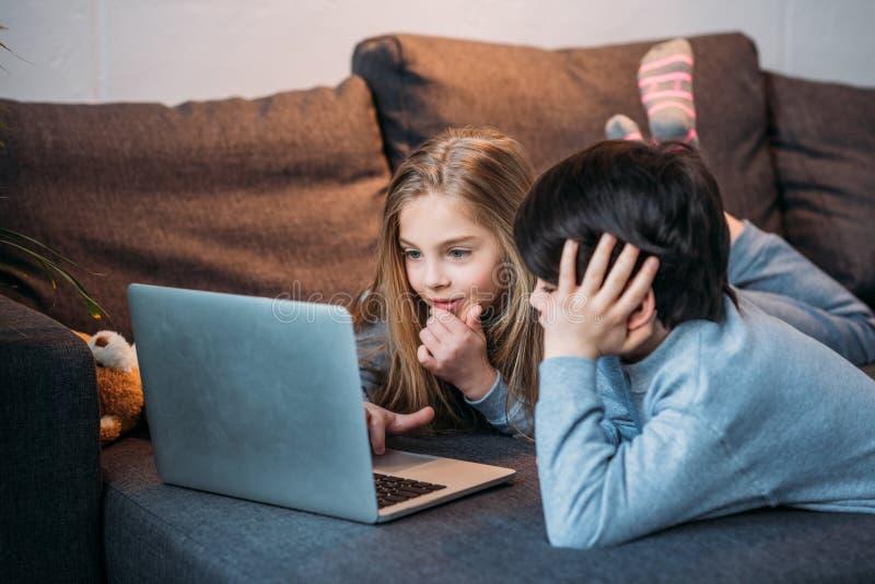 Aanbiddelijke gelukkige meisje en jongen gebruikend laptop en liggend op bank stock afbeeldingen