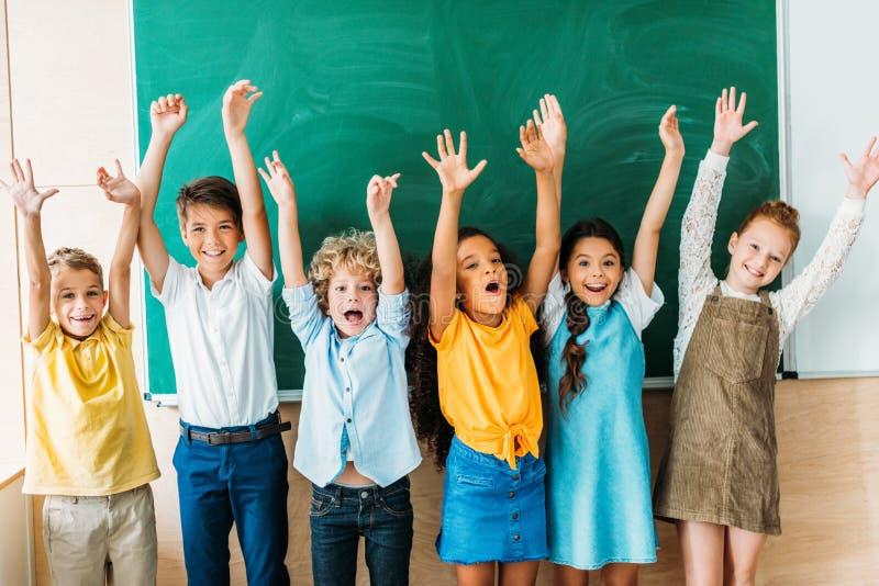 aanbiddelijke gelukkige schoolkinderen met opgeheven handen die bevinden zich voor stock fotografie
