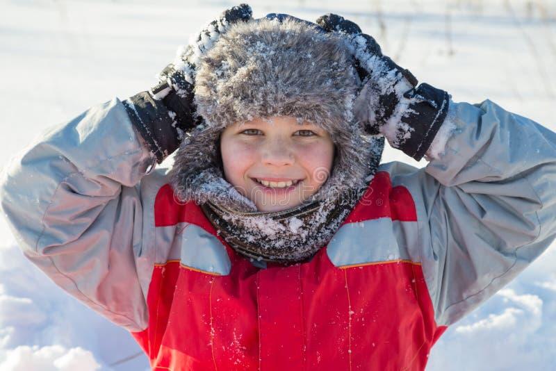 Aanbiddelijke glimlachende jongen bij de sneeuwachtergrond royalty-vrije stock foto