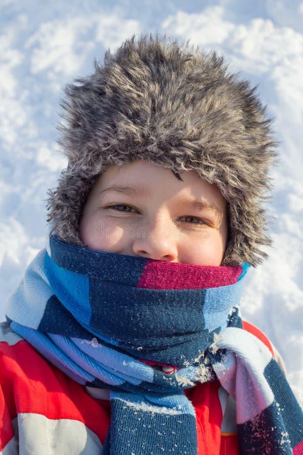 Aanbiddelijke glimlachende jongen bij de sneeuwachtergrond royalty-vrije stock afbeelding