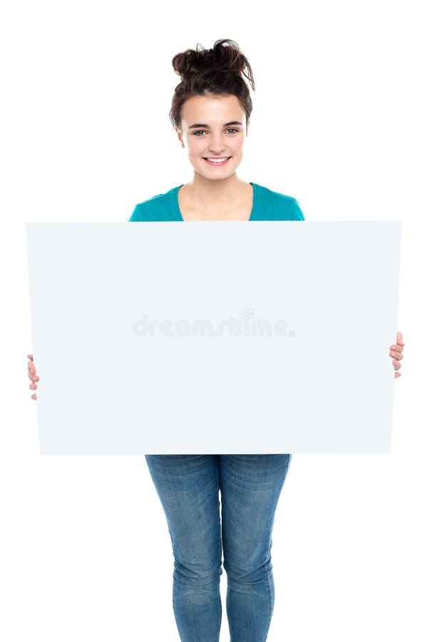 Aanbiddelijke glimlachende tiener die grote advertentieraad houdt royalty-vrije stock afbeeldingen