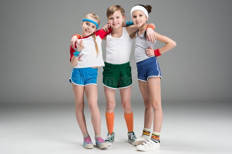 Aanbiddelijke het glimlachen sportieve jonge geitjes in sportkleding die zich op grijs verenigen royalty-vrije stock afbeelding