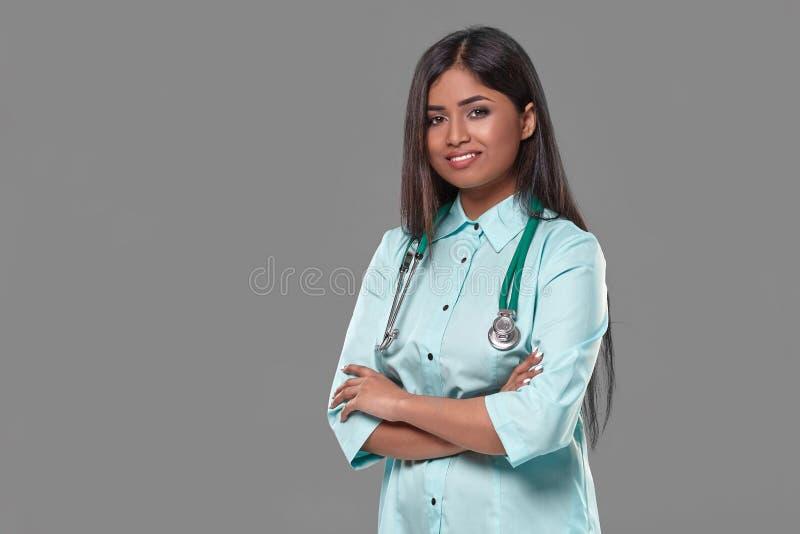 Aanbiddelijke Indische vrouwelijke artsenverpleegster met stethoscoop in aquamarijnkleding op grijze achtergrond royalty-vrije stock foto