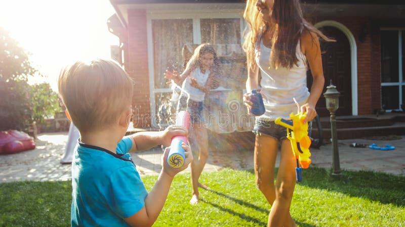 Aanbiddelijke 3 jaar het oude van de peuterjongen bespattende water van plastic stuk speelgoed kanon bij huisbinnenplaats Kindere royalty-vrije stock foto