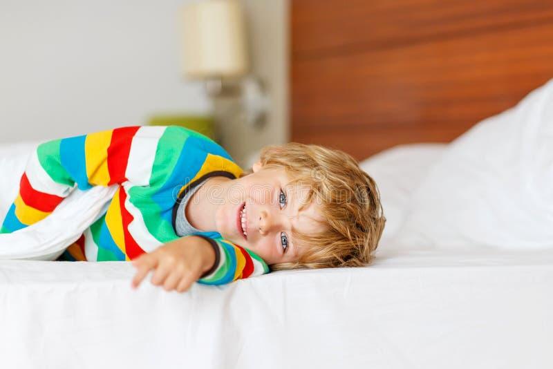 Aanbiddelijke jong geitjejongen na het slapen in zijn wit bed stock foto