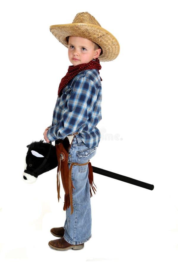 Aanbiddelijke jonge cowboy die een werious gezicht van het stokpaard berijden royalty-vrije stock foto