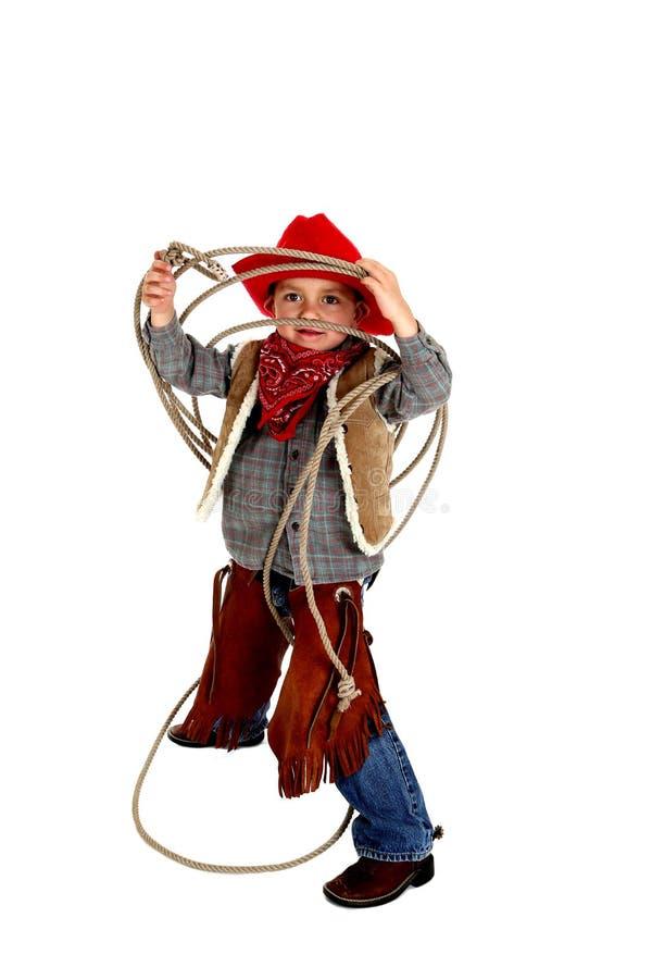 Aanbiddelijke jonge cowboy die kloofjes, laarzen, en hoed het spelen dragen met royalty-vrije stock foto's