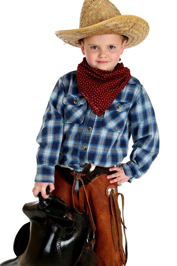 Aanbiddelijke jonge cowboyhanden op het zadel van de heupholding stock foto's