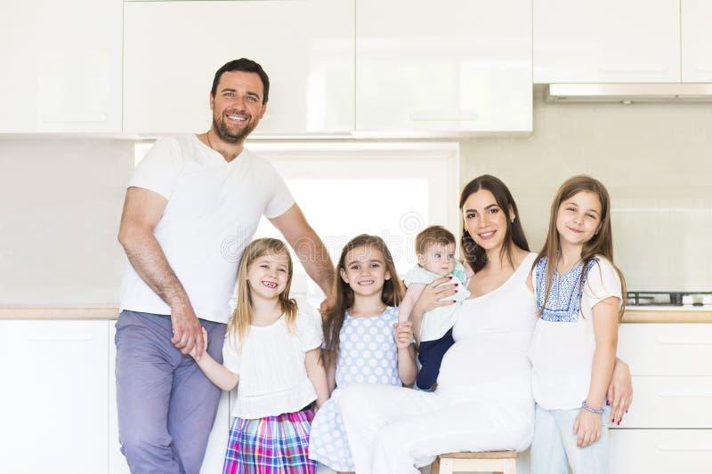Aanbiddelijke jonge grote familie die op keuken omhelzen stock afbeeldingen