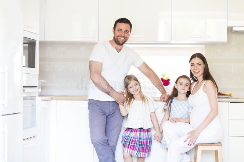 Aanbiddelijke jonge grote familie die op keuken omhelzen stock foto's