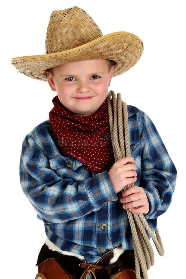 Aanbiddelijke jonge jongen die de holdingskabel dragen van de cowboyhoed stock fotografie