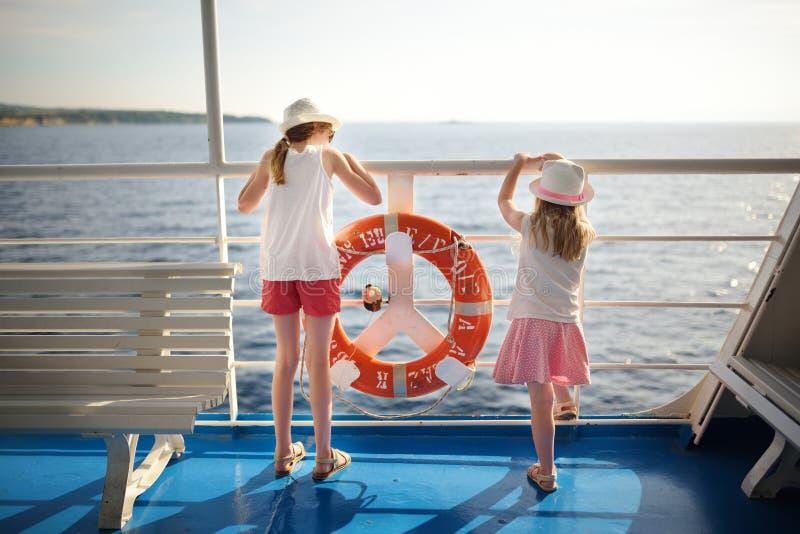 Aanbiddelijke jonge meisjes die veerboot van rit genieten die bij het overzees op zonsondergang staren Kinderen die pret op de va royalty-vrije stock foto's