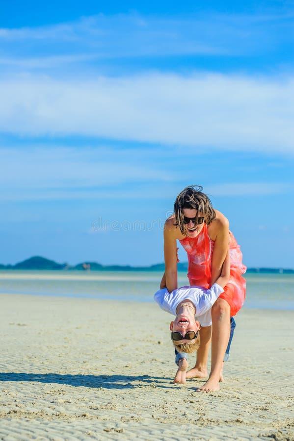 Aanbiddelijke jongen die pret met zijn mamma op het tropische strand hebben Witte t-shirt, donkere broeken en zonnebril Blootvoet stock foto