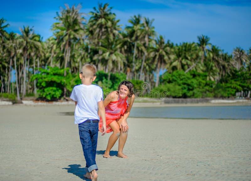 Aanbiddelijke jongen die pret met zijn mamma op het tropische strand hebben Witte t-shirt, donkere broeken en zonnebril Blootvoet royalty-vrije stock fotografie