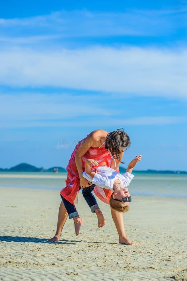 Aanbiddelijke jongen die pret met zijn mamma op het tropische strand hebben Witte t-shirt, donkere broeken en zonnebril Blootvoet stock afbeeldingen