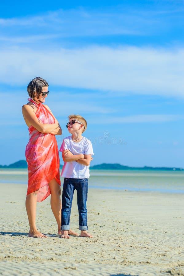 Aanbiddelijke jongen die pret met zijn mamma op het tropische strand hebben Witte t-shirt, donkere broeken en zonnebril Blootvoet royalty-vrije stock foto