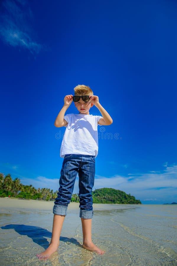 Aanbiddelijke jongen die pret op het tropische strand hebben Witte t-shirt, donkere broeken en zonnebril Blootvoets op wit zand royalty-vrije stock foto's