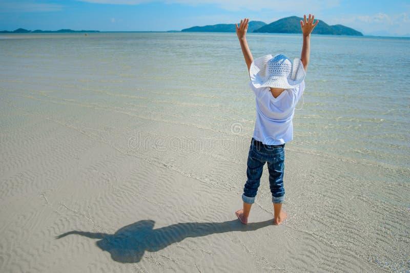 Aanbiddelijke jongen die pret op het tropische strand hebben Witte t-shirt, donkere broeken en zonnebril Blootvoets op wit zand royalty-vrije stock afbeelding