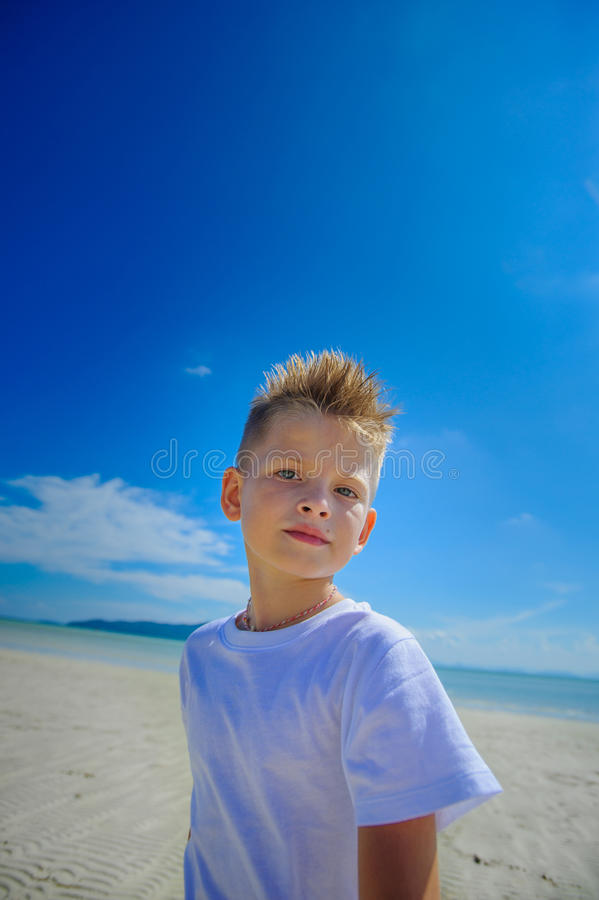 Aanbiddelijke jongen die pret op het tropische strand hebben Witte t-shirt, donkere broeken en zonnebril Blootvoets op wit zand stock foto's