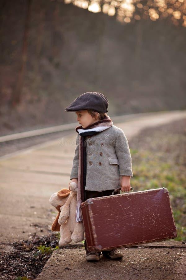 Aanbiddelijke jongen op een station, die op de trein met koffer en teddybeer wachten royalty-vrije stock fotografie