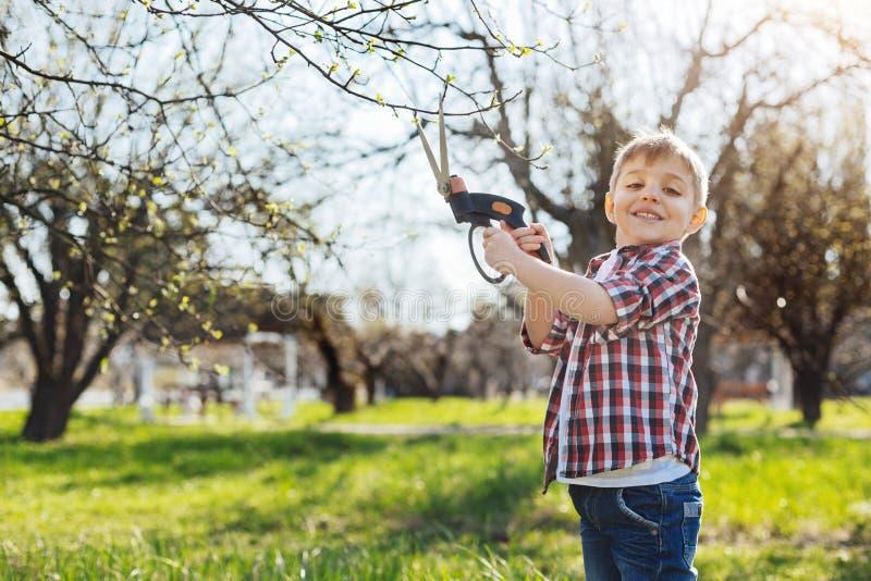 Aanbiddelijke jongensholding snoeischaar en het glimlachen royalty-vrije stock foto